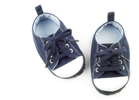 A tiny pair of blue infant shoes for a boy, isolated on white background with copy space photo
