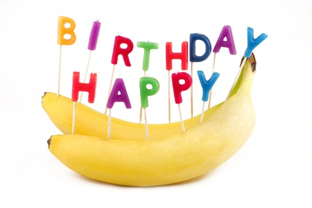 Two yellow bananas with Happy Birthay Letter candles instead of cake for healthy lifestyle birthday, isolated with white background and copy space photo