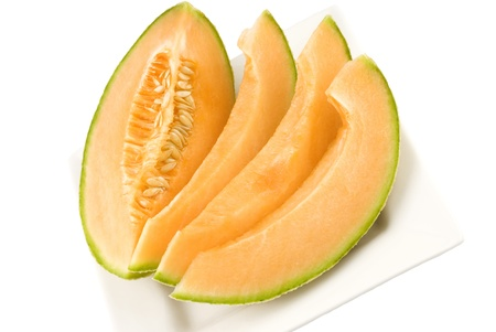 Fresh sliced cantaloupe on a plate with white background and copy space