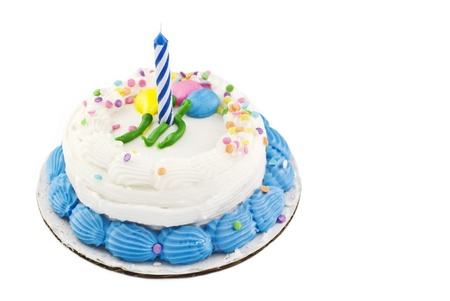 piped: A small white birthday cake with balloon decoration and candy sprinkles, one unlit candle