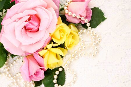 Beautiful pink and yellow roses with pearls on a lace background, perfect for Mothers Day!