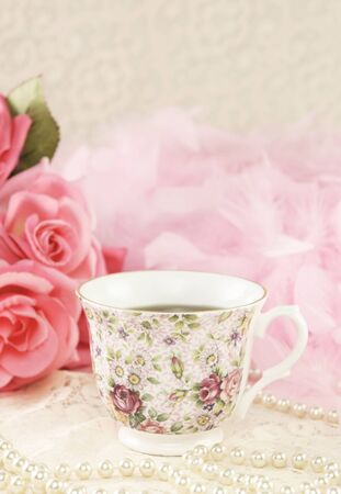 A delicious cup of tea in a floral china teacup with roses, pearls and pink boa in background, selective focus on teacup Imagens