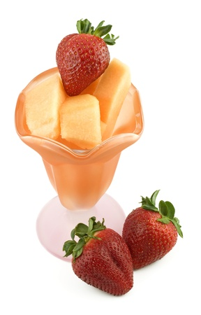 cubed: A orange and pink glass parfait dish filled with cubed cantaloupe and fresh whole strawberries, isolated on white background, copy space Stock Photo