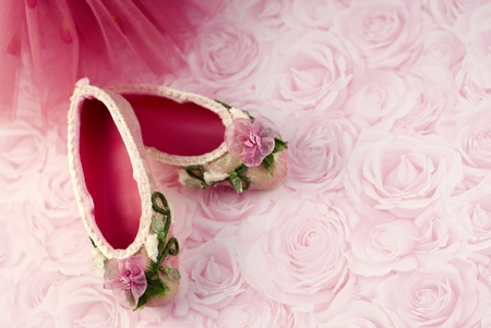 Pink ballet slippers with tutu on rose background with copy space