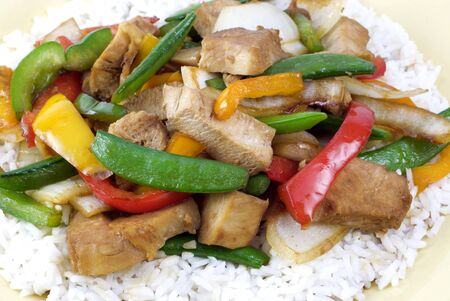stir fry: Teriyaki Chicken stir-fry on a bed of rice with colorful peppers and onions Stock Photo