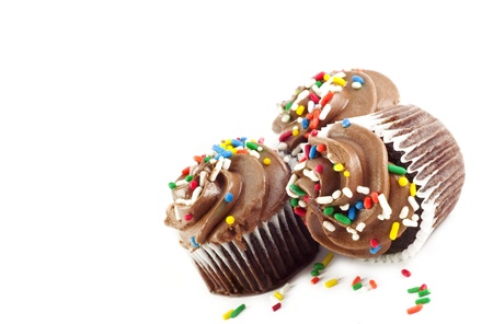 Three delicious chocolate cupcakes with chocolate frosting and colored sprinkles on white background diagonal with copy space and selective focus Imagens