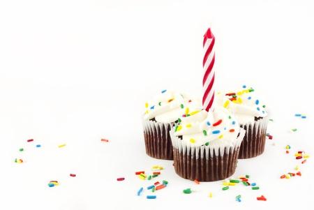 Drei chocolate Cupcakes mit Vanille Zuckerguss und Sprinkles mit einem roten Kerze unbeleuchteten auf weißem Hintergrund mit textfreiraum