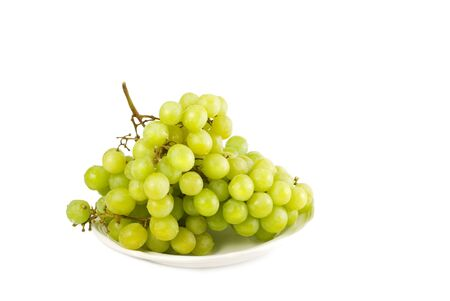 Cluster of green grapes on a plate isolated on white background with copy space photo