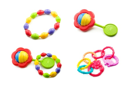 teething: A collage of baby toys including teething rings, and rattles isolated on a white horizontal background Stock Photo