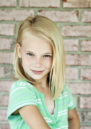 A cute little blonde haired girl, looking at camera