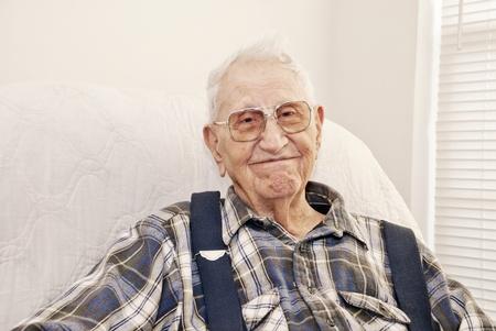 コピー スペースを持つ彼の家、クローズ アップで椅子に座っている老人