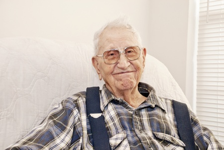 An elderly man sitting in a chair at his home, closeup with copy space Stock Photo
