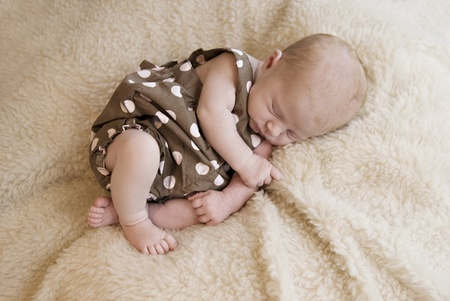 A three week old baby girl sleeping, soft focus photo