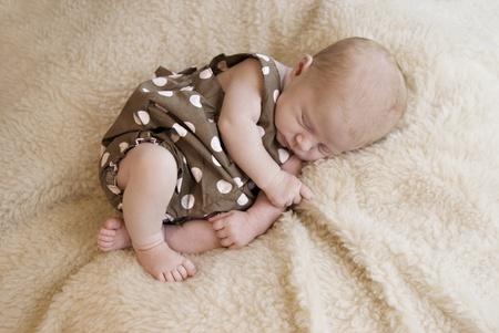 A three week old baby girl sleeping, soft focus