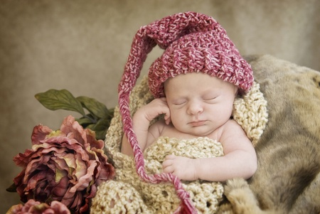 A sleeping newborn baby girl in chocetted cocoon wearing hat with vintage looking setup, selective focus with focus on face