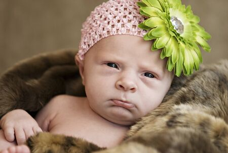 A closeup of a cute frowning baby girl wearing hat with flower, selective focus with shallow depth of field photo