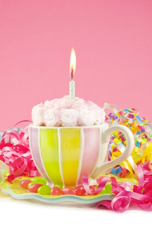 A pink birthday cupcake in a multicolored teacup, with birhtday decorations, pink background, vertical with copy space Imagens