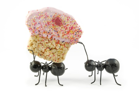 Two toy black ants carrying a crispy cereal cupcake, concept, isolated on white background, horizontal with copy space, cute