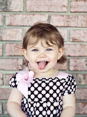 A cute little girl sticking out her tongue, vertical with copy space, natural light