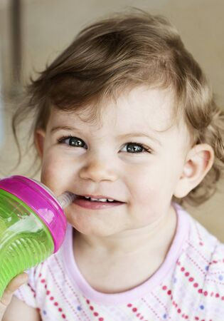 A cute little girl drinking from a sippy cup, selective focus on face