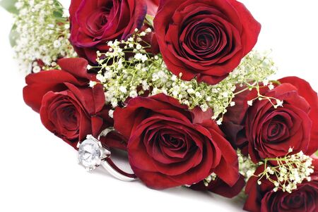 A sparkling diamond engagement ring with a bouquet of red roses, white background with copy space