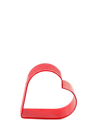 A metal red heart cookie cutter on a vertical white background with copy space photo
