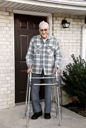 disable: A 93 year old handicapped man, with a walker, standing outside in front of his apartment Stock Photo
