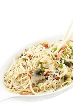 Chinese rice noodles with chicken and vegetable stir-fry in a dish with chopsticks, white vertical background photo