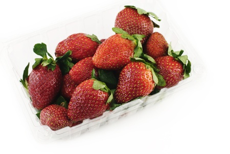 Fresh strawberries in a plastic container on a white background, top view photo