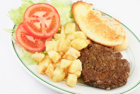 A delicious juicy hamburger steak with seasoned diced potatoes, sliced tomatoes and toasted bread on a platter, top view, white background photo