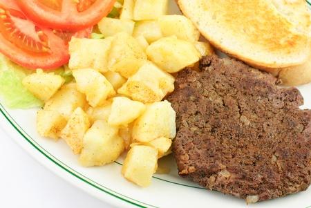 Delicious hamburger steak with onions, diced seasoned potatoes, closeup photo