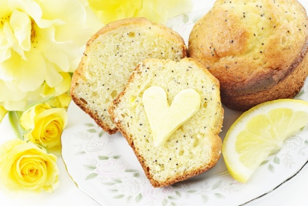 A plate with fresh baked lemon poppy seed muffins with heart shaped butter on muffin, concept Фото со стока - 9129802