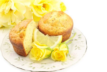 A plate of Lemon Poppy Seed Muffins with bright yellow roses, white background