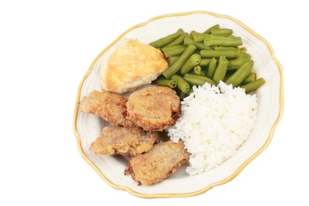 A dinner plate with fried pork tenderloin, green beans, white rice and biscuit, top view, isolated in white background photo
