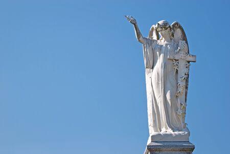 memorial cross: Estatua del �ngel mujer de m�rmol blanco con Cruz, brazo y mano planteadas con espacio de copia de fondo de cielo azul s�lido Foto de archivo