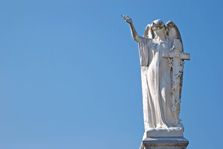 angel headstone: White marble woman angel statue with cross, arm and hand raised with solid blue sky background copy space