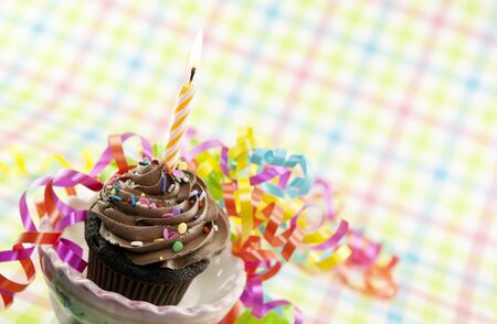 A delicious chocolate cupcake with one lit candle and colorful party ribbons Stock Photo - 9171031