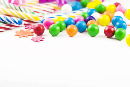 gumballs: Party supplies, candles, gumballs, colored shapes, spilled on whilte background copy space Stock Photo