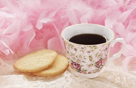 A pretty floral teacup with tea and homemade sugar cookies with pink boa in background, selective focus on teacup photo