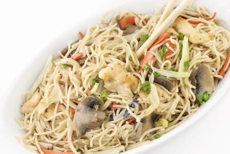 Chinese chicken and vegetable stir-fry with rice noodles, chicken, mushrooms, cabbage, carrots, with chopsticks, top view photo