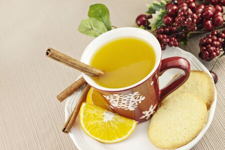 spiced: A cup of hot spiced fruit Wassail holiday punch with a cinnamon stick and homemade sugar cookie