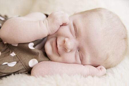 A closeup of a sleeping three week old baby girl smiling, soft focus photo