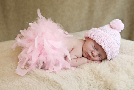 pink hat: A sleeping baby girl wearing pink hat and pink feather boa, soft focus