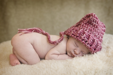 A sleeping baby girl wearing a hat, soft focus