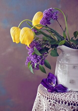 A beautiful spring flower arrangement with yellow tulips and lilac in a vase, low light still life photo