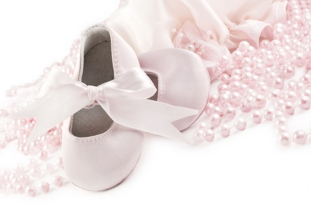 A pair of pink baby shoes with pink pearls on a white horizontal background with copy space photo