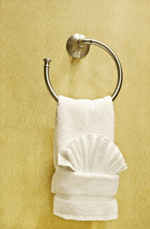 An fancy folded hotel towel on a towel holder on the wall, vertical with copy space Imagens