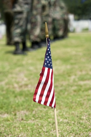 military cemetery: An American flag with Army soldiers blurred in background, ceremony on Memorial Day at National Cemetery, shallow depth of field