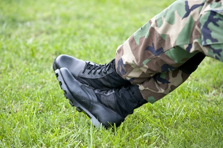 A US Army soldier wearing camouflage resting with just a closeup of his legs and boots, selective focus on boots photo