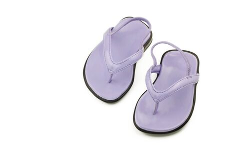 A tiny pair of newborn purple shoes or sandals for a girl, isolated on white with copy space photo